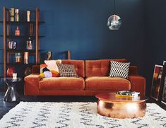 Inspiration - Yuba Mercantile - Inspiration I'm so into moody rooms with dark paint colors. In this one the rust orange couch contrasted with the dark blue walls and black and white Moroccan style rug creates an envy-inducing mood! Blue Velvet Couch, Orange Couch, Green Velvet, Velvet Corner Sofa, Orange Rooms, Living Room Orange, Bold Living Room, Chaise Sofa, 2 Seater Sofa