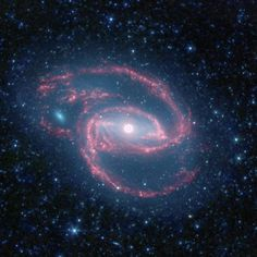 """Galaxy NGC 1097 (photo by NASA's Spitzer Space Telescope)- the """"eye"""" that seems to be at the center of the galaxy is actually a supermassive black hole surrounded by stars!"""