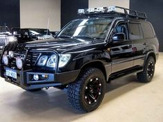 2005 Lexus LX470 4x4 Custom: An Ultra Luxury Version of the LEGENDARY Land Cruiser (100). A PRO LvL Engine Tune-Up, Suspension System upgrade and the inclusion of a staged Twin Turbo Package as well as an aggressive body kit with matching alloy rims maximize the LX470's appeal as incredibly off-road capable Urban carrier. Whether exploring the snow covered mountain roads of Colorado or raiding the mall with friends this HARDENED LX470 will get you there.