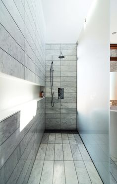 """The standing shower is set off by etched-glass panels supported by stainless-steel hardware. There is no threshold; instead, the tile within the shower zone slopes down very slightly to a floor trough with a custom stainless-steel grille. Along the wall, a Corian shelf—""""the longest soap dish in the world,"""" resident Don Evans jokes—runs the length of the space."""