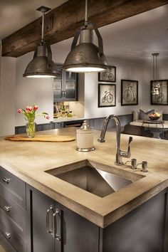 Industrial farmhouse kitchen. Here  I like the modern island but the rustic beam and recycled lighting.