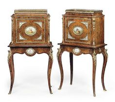 A PAIR OF ENGLISH BURR-WALNUT ORMOLU AND TURQUOISE-GROUND PORCELAIN-MOUNTED CABINETS-ON-STANDS<br />MID-19TH CENTURY <br />The tapering pediment surmounted by a gallery, above a door centred by an oval porcelain plaque painted with a rustic scene, on a shaped apron with cabriole legs headed by acanthus-wrapped caryatids<br />48 in. (121.9 cm.) high; 26¾ in. (68 cm.) wide; 15¾ in. (40 cm.) deep (2)<br />