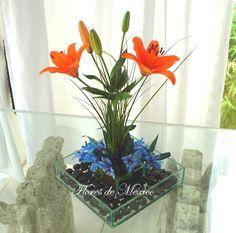 Elegante arreglo de lilis y exóticas flores azules, dispuestas en base cuadrada de vidrio rodeadas por piedra negra de río.     Perfecto para un detalle de agradecimiento o cualquier ocasión.     Dimensiones: Base 33cm X 55 cm alto.