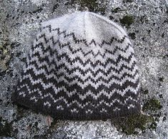 A hat to wear for wintry walks. A windy snowfall and fir trees half dark, half white are translated into a stylized motif. Knitted in a natural black and light grey Finnsheep wool yarn.