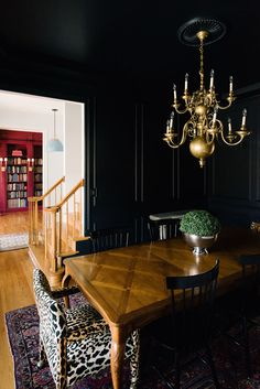 Black walls and black ceiling. Such a dramatic dining room with a beautiful brass chandelier over an antique table.