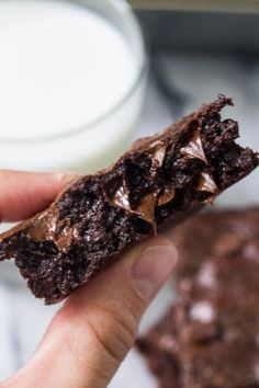 Close up side view of chewy brownie with melted chocolate chips held between 2 fingers. Glass of milk and plate of brownies in background.