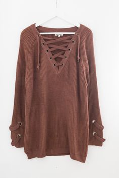 """- Chunky knit sweater tunic - Lace-up front - Long sleeves with criss-cross strap side detailing - Slightly loose fit - Size S/M measures approx. 31"""" in length - 55% Cotton 45% Acrylic - Imported"""