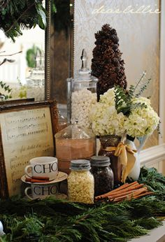 Hot Chocolate Bar decorated with real garland and cinnamon sticks, plus a sheet of Christmas music