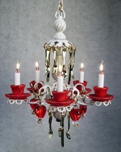 Teacup chandelier in antique white with red teacups and saucers and red glass hearts and hanging silver utensils.