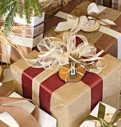 These charming gifts are wrapped in the same burlap fabric used for the stockings. The gifts were then adorned with natural elements like wood tags paired with bronze filigree ornaments