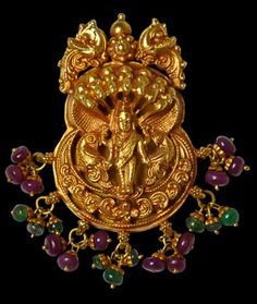 This fine pendant of repoussed and hammered gold sheet shows the deity Meenakshi, the South Indian avatar of the goddess Parvati. The two pairs of parrots shown with the goddess suggest her identity as being Meenkashi.