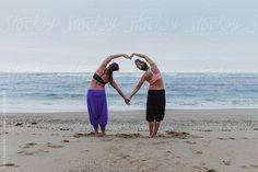 women doing yoga exersices on the beach by Thais Ramos Varela for Stocksy United