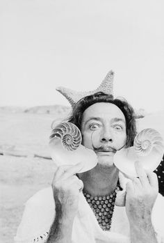 Spanish surrealist artist Salvador Dali (1904 - 1989) holds up two seashells at his home in Cadaques on the Costa Brava, Spain, 8th January 1955. Photo by Charles Hewitt. °