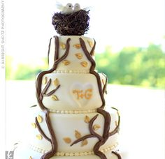 "Brown fondant tree branches laced with gold leaves sprawled out across the four-tiered, monogrammed confection. ""We thought it would go well with an outdoor simple wedding while revealing a little of our love for nature and hiking,"" says Tara. A small twi..."