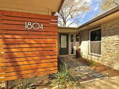 under stairs in front slatted screen with house numbers mid century modern modern austin architecture design of central texas