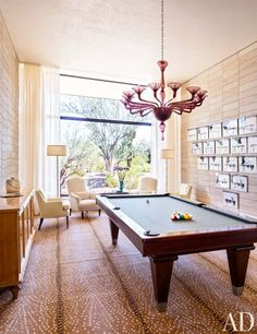 In the game room of an Arizona home, a Blatt Billiards pool table is set on a Stark carpet beneath a vintage Murano-glass chandelier; the multipart artwork is by Robin Rhode.  ARCHITECT: Marwan Al-Sayed DESIGNER: Jan Showers PHOTOGRAPHER: Scott Frances