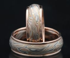 "MATCHING PAIR OF VERY RED GOLD WEDDING BANDS H2CL210-7 H2: Mokume of 14K palladium white gold, 14K red gold and sterling silver with higher proportion of 14K red gold C: Domed comfort fit L: Lightly etched 210: 14K red gold round rails and no liner 7: Shown in width of 7mm Fill out the form for … Continue reading ""MATCHING PAIR RED GOLD WEDDING BANDS h2cl210-7"""