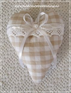 Simple heart without bows and other seasonal stuffed items like white pumpkins w/brown embroidery creases and strings to hang from a button sewn at the center of a valance or swag on my new porch windows would be divine; particularly if those valances were reversible gingham one side muslin the other. How quaint and lovely. Apples & gingham for September. Patriot stars for Memorial Day through July. White Daisies for summer, etc.