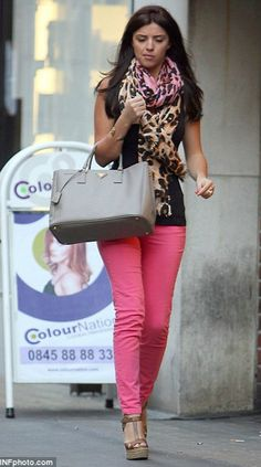 Pink jeans, tan wedges, a black vest and scarf.