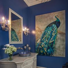 Two ornate metal sconces flank a white framed mirror in this blue traditional powder room. Tall ceilings and a neutral vanity help to balance the more standout elements of the space, including the vibrant peacock artwork.