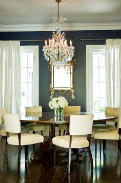 dining room dark walls white curtains round table chandelier
