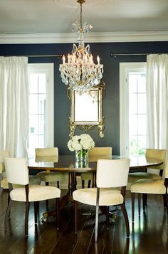 dining room dark walls white curtains round table chandelier