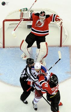 New Jersey Devils goalie Brodeur falls back on his net after being hit by New York Rangers' Rupp as he is grabbed by an official and New Jersey Devils' Volchenkov in Game 4 of their NHL Eastern Conference Final hockey playoff game in Newark