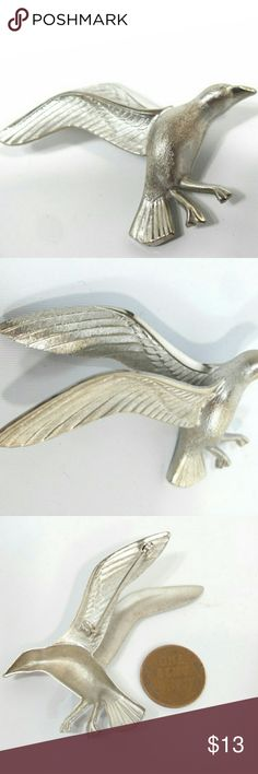 Bird Brooch Vintage Bird Silver Tone Brooch This vintage bird brooch measures 2 1/2 inches long, it is silver tone with 3-dimensional wings.  There are no makers marks.  The back is hollow the front looks as if it is etched.  This is a wonderful unique gift for a brooch wearing bird lover. vintage Jewelry Brooches