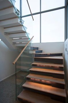 Steel Studio Staircase with frameless glass balustrades and timber toprail