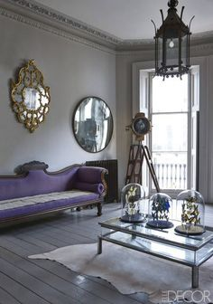 Brighton England Antique Townhome - Seaside English Home - ELLE DECOR An 18th-century Rococo-style English mirror and a 20th-century convex mirror hang above an Irish Regency sofa; the cocktail table is 20th century, and a ship's searchlight from the 1900s is mounted on a military tripod base; the walls are painted in Elephant's Breath and the floor in Charleston Gray, both by Farrow & Ball.
