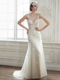 Maggie Sottero - DEMI, The perfect combination of elegance and romance combine in this tulle slim A-line wedding dress, complete with three-dimensional floral appliqués, sparkling Swarovski crystals, and illusion tank sleeves. Intricate patterns of Swarovski crystals adorn an unexpected sheer plunging back. Finished with crystal button over zipper closure.