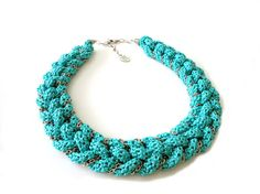 This trendy knot necklace was created by knotting crocheted tube cord in blue color. Silver tone chain was coiled through the knots as accent. The