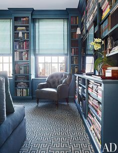 Dark blue walls and large bookshelves surround the living room