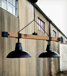 Huge industrial-style chandelier made with a recycled wood beam and black lamp shades. The contrast of black metal and old wood makes this lamp unique and chic.