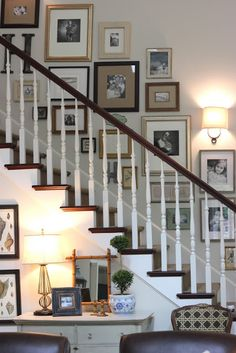 """This is a beautiful take on the classic """"frames running up the stairs"""" concept. I love how it pops off the wooden staircase, and the sconce is well placed."""