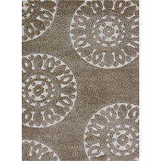 This Jullian rug features a durable power-loom construction and a thick one-inch pile. This shag rug features varying pile heights for added texture and a beige and ivory abstract design.