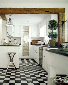 In the Connecticut kitchen of accessories designers Richard Lambertson and John Truex, white cabinetry and soapstone counters echo the palette of the checkered tumbled-marble floor beneath. A rough-hewn beam provides a woodsy touch to the country kitchen, while a factory stool from London adds industrial chic to the tailored space.
