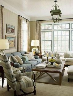 living room; Sage green walls, light blue sofa warm wood coffee table. Also the aqua marine blue trim on windows.