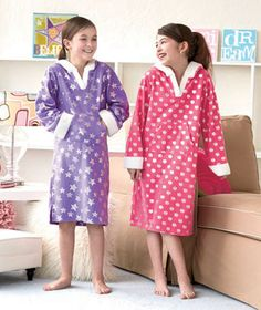 This super soft Girls' Fleece Nightgown with Hood is a fashionable way to stay warm on cold nights. Perfect for lounging, sleeping or a slumber party with friends, these long-sleeved, pullover gowns have a shiny, foil-printed pattern on a solid backg