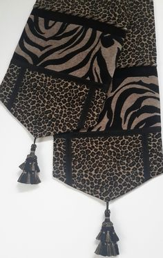 Elegant table runner in leopard and zebra print chenille fabrics with black velvet inset, chenille decorative trim, and 5 inch. The table runner is lined in black satin with an embroidered fleur-de-lis pattern. Size: x 72 in