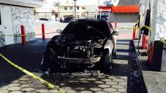 Los Angeles Fire Department investigators cordoned off the remains of a burned car after suspects set it on fire at a gas station on Saturday, April 11, 2015.