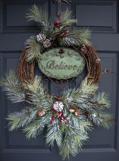 Rustic Christmas Wreaths  Outdoor Holiday by HomeHearthGarden Here is a Rustic Christmas Wreath handmade with artificial pine boughs, pine cones, holiday berries, and an antiqued looking sign 'BELIEVE'.   Wreath measurements: 22-24 inches overall width at the tips of the pine branches; 31 - 33 inches tall from the bottom of the pine branches to the top of the pine branches.  Wreath depth is approximately 6 inches. #rustic Christmas #wreath #wreaths #Christmaswreath #holidaydecor