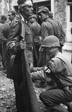 A US MP of the Armored Division with a SS soldier of Panzergrenadier Division Götz von Berlichingen, Caen, Normandy, France (Photo by Robert Capa) Capa who is buried in Caen. Hiroshima, Nagasaki, German Soldiers Ww2, American Soldiers, Vietnam, World History, World War Ii, Omaha Beach, First Indochina War