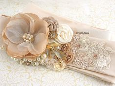 ***Made Upon Request- This bridal sash can be made in ANY color scheme  This stunning piece features an elegant blend of soft tones: champagne, nude, latte, ivory and gold. This vintage-inspired piece displays a pretty focal flower crafted with champagne taffeta, ivory tulle and sewn pearls and crystals. Satin rosettes in nude and shades of ivory, along with a pretty vintage brooch set in gold and my signature cluster of pearls and crystals frame the focal bloom. The piece has been finished…