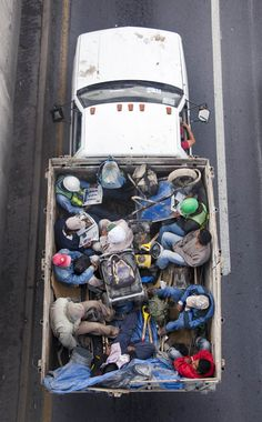 aerial birds eye view of people riding car pooling in back of pickup trucks from above alejandro Cartagena (4)