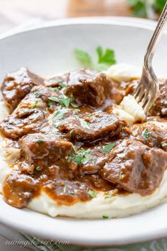 A bowl of mashed potatoes topped with tender Beef Tips in a rich, flavorful gravy filled with mushrooms and onions.
