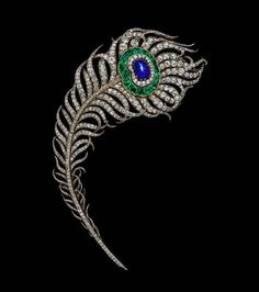 twentyonejewelsBoucheron, c. 1880 A French late 19th century multi gem-set brooch, realistically modelled as a peacock's feather, the curved shaft and vane set with old-cut diamonds, the 'eye' centrally-set with a cabochon star sapphire within a diamond-set border to the outer surround of calibre-cut emeralds, mounted in silver and yellow gold. Albion Art Collection, Tokyo, Japan.