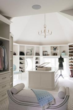 Expansive custom walk-in closet features a beaded chandelier hung from a vaulted ceiling over a mirror top white island topped with a jewelry cabinet. The island is surrounded by white modular bag and shoe shelves mounted framing windows. The closet is completed with a blue ikat round back chair and a gray linen settee with a nailhead trim. Design - Vincente Longo Custom Builders