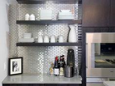 Sparkling stainless backsplash with dark cabinetry.