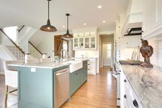 A pair of black vintage barn pendants hang over a green blue kitchen island accented with beadboard trim topped with gray and white granite fitted with a sink next to a stainless steel dishwasher lined with linen slipcovered counter stools atop a white oak floor.